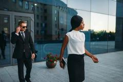 女商人,衣服的保镖在背景 免版税库存照片