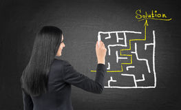 女商人画一个迷宫用在白垩黑板的解答 库存照片