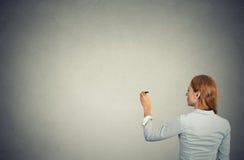 女商人从在墙壁上的后面文字射击了 免版税库存照片