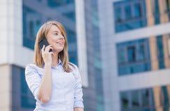女商人画象户外谈话在有现代大厦的电话作为背景 免版税图库摄影