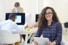 年轻女商人画象现代起始的办公室内部的,队在会议在背景中 库存图片
