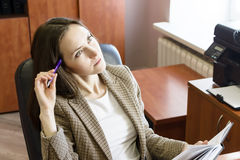 年轻女商人画象,认为与笔和笔记薄在办公室 免版税库存照片