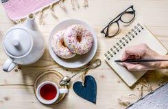 女商人` s构成用茶和油炸圈饼 在书桌的快餐 办公室桌书桌 家庭办公室工作场所 库存照片