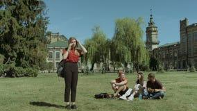 女大学生谈话在校园草坪的巧妙的电话 股票录像