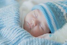 女婴与一个被编织的帽子婴孩睡觉 图库摄影