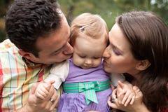 女婴亲吻爱做父母他们 免版税库存图片
