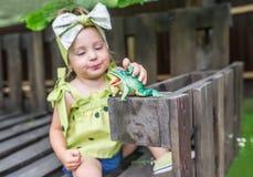 女婴使用与玩具青蛙 在玩具青蛙的有选择性的fokus 图库摄影