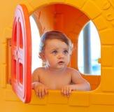 女婴使用在海滩在一个微型房子里 免版税库存图片