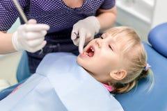 女婴参观的口腔医学诊所 做核对的牙医孩子牙 儿童牙和嘴医疗保健 库存图片