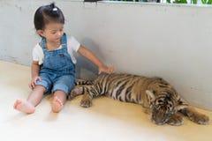 女婴和小老虎在公园 免版税库存照片