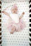 女婴在与一条蓬松桃红色裙子的床上哭泣 反复无常的子项 哭泣的婴孩顶视图 免版税库存照片