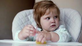女婴在与眼泪汪汪的眼睛的高脚椅子在慢动作坐关闭  股票录像