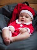 女婴在圣诞老人服装在枕头中坐并且微笑 免版税库存照片