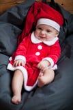 女婴在圣诞老人服装在枕头中坐并且微笑 库存照片