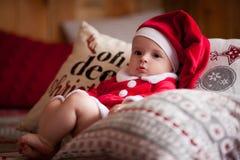 女婴在圣诞老人服装在枕头中坐 免版税库存图片