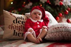 女婴在圣诞老人服装在枕头a中坐并且微笑 库存图片