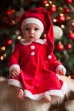 女婴在圣诞老人服装坐毛皮地毯反对backgro 免版税库存照片