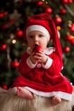 女婴在圣诞老人服装坐毛皮地毯并且拿着克里斯 库存图片