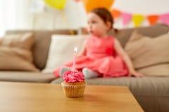 女婴在家党的生日杯形蛋糕 图库摄影