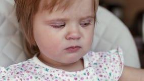 女婴在高脚椅子坐并且吃干燥面团关闭在慢动作 股票视频