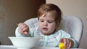 女婴在高脚椅子坐并且吃面团关闭匙子在慢动作 股票录像