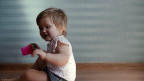 女婴坐地板,微笑和转动在慢动作的一个圈子 影视素材