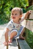 女婴坐她的在长凳的腰臀部分 库存照片