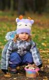女婴坐腰臀部分和一个桃红色桶真菌/蘑菇在秋天森林里 免版税库存图片