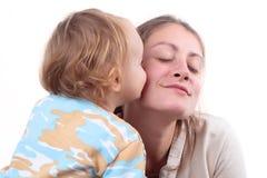 女婴她亲吻的母亲 免版税库存图片
