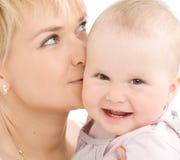 女婴她的亲吻母亲 库存图片