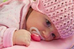 女婴戴一个桃红色帽子 免版税库存照片