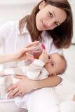 女婴拿着她的母亲 免版税库存图片