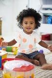 女婴画象获得乐趣在与玩具的游戏室 库存图片