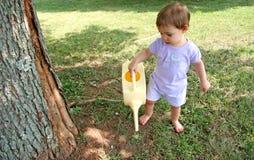 女婴草坪浇灌 库存照片