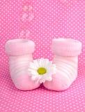 女婴被编织的桃红色鞋子袜子 免版税库存照片