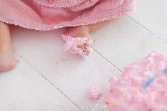 女婴跨步在蛋糕在她的生日庆祝时-特写镜头射击的腿脚 蛋糕抽杀第一个年概念 免版税库存照片