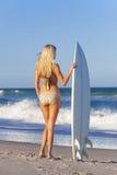 女子冲浪者有冲浪板的女孩比基尼泳装在海滩 免版税库存照片