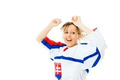 女子在球衣的冰球迷在斯洛伐克欢呼的全国颜色,庆祝目标 免版税图库摄影