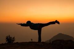 女子实践的瑜伽剪影 免版税库存照片