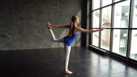 女子实践的瑜伽在一个明亮的演播室,流经太阳致敬 女性做的瑜伽在有自然的一个演播室 股票视频