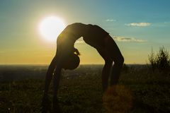 女子实践的瑜伽在日落的公园-滴下,轮子姿势 免版税库存照片