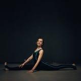 女子实践的瑜伽对黑暗的被构造化的墙壁 免版税库存图片