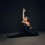 女子实践的瑜伽对黑暗的被构造化的墙壁 免版税库存照片