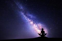 女子实践的瑜伽的银河和剪影 库存照片