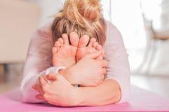 女子实践的瑜伽,今后供以座位的弯姿势,做paschimottanasana锻炼 库存照片