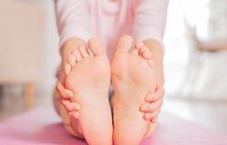 女子实践的瑜伽,今后供以座位的弯姿势,女性脚 库存图片