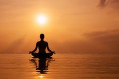 女子实践的瑜伽,在海滩的剪影在日落 免版税图库摄影