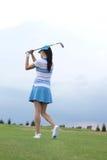 女子摇摆的高尔夫俱乐部背面图在路线的 库存图片