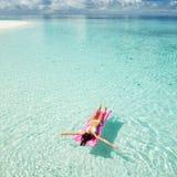 女子游泳和在可膨胀的床垫放松在海 免版税库存图片