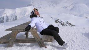 女子滑雪者乐趣放松在山在一个晴天坐长凳 图库摄影